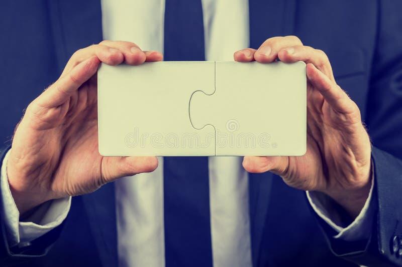 Homem de negócios que guarda duas partes bloqueadas do enigma imagens de stock
