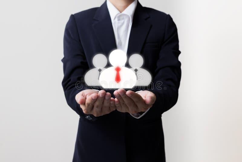 Homem de negócios que guarda gerentes e símbolos da equipe imagem de stock