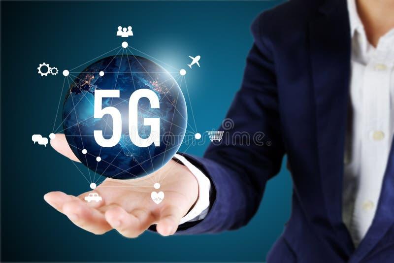 Homem de negócios que guarda global com ícones da rede 5G 5G tecnologia c imagem de stock