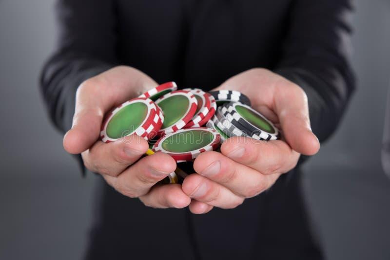 Homem de negócios que guarda microplaquetas de pôquer nas mãos colocadas foto de stock