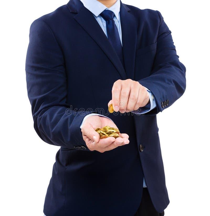 Homem de negócios que guarda a moeda de ouro fotos de stock royalty free