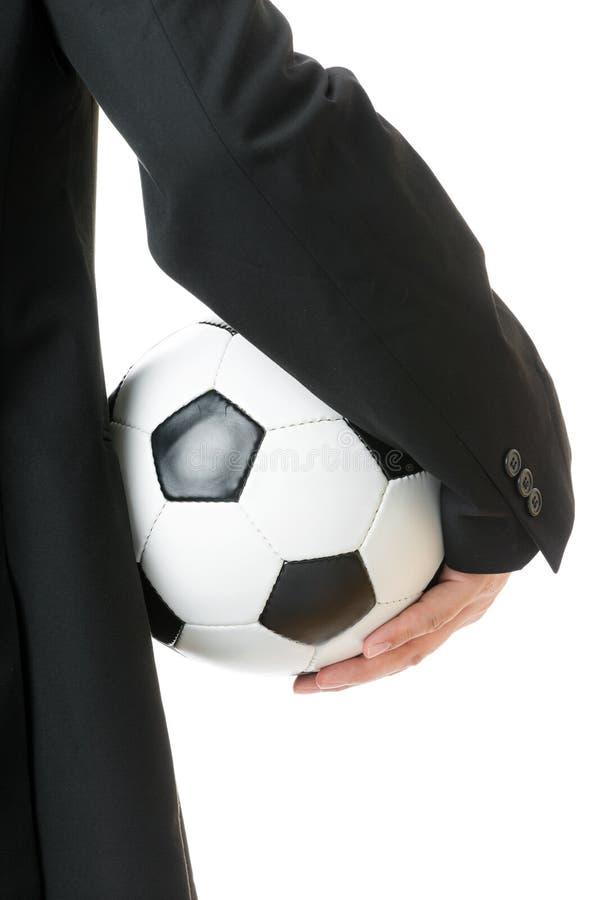 Homem de negócios que guarda o bal do futebol foto de stock