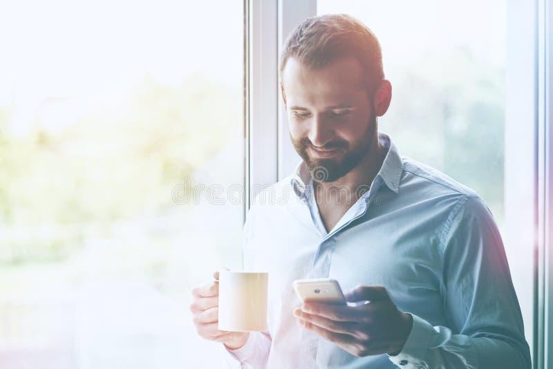Homem de negócios que guarda o café e que lê o telefone imagem de stock royalty free