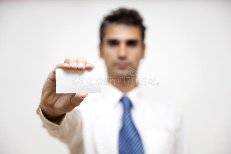 Homem de negócios que guarda o cartão branco em sua mão fotografia de stock