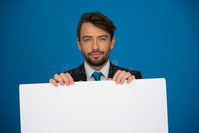 Homem de negócios que guarda o cartaz vazio fotografia de stock royalty free