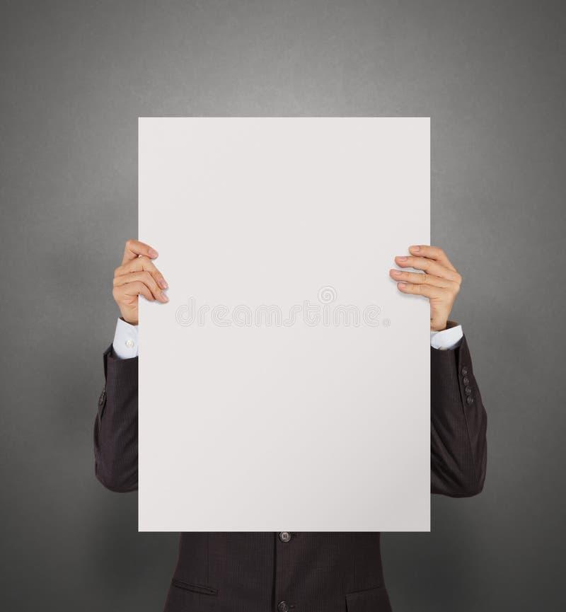 Homem de negócios que guarda o cartaz vazio na parede da textura fotografia de stock royalty free