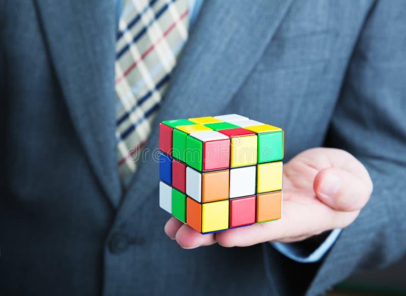 Homem de negócios que guarda o cubo do rubik em suas mãos fotografia de stock royalty free