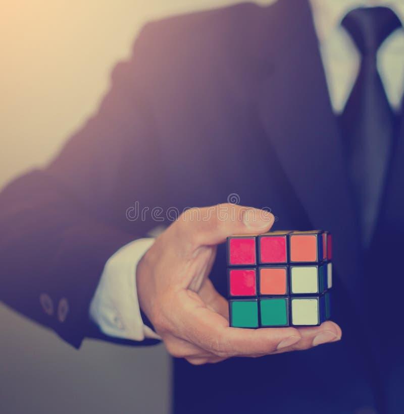 Homem de negócios que guarda o cubo de Rubik imagem de stock royalty free