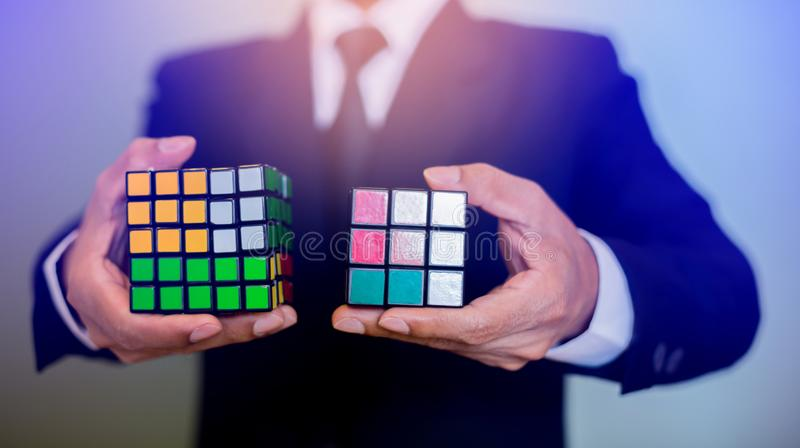 Homem de negócios que guarda o cubo de Rubik fotos de stock