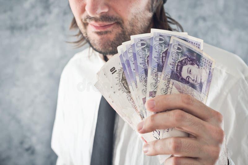 Homem de negócios que guarda o dinheiro das libras britânicas imagem de stock