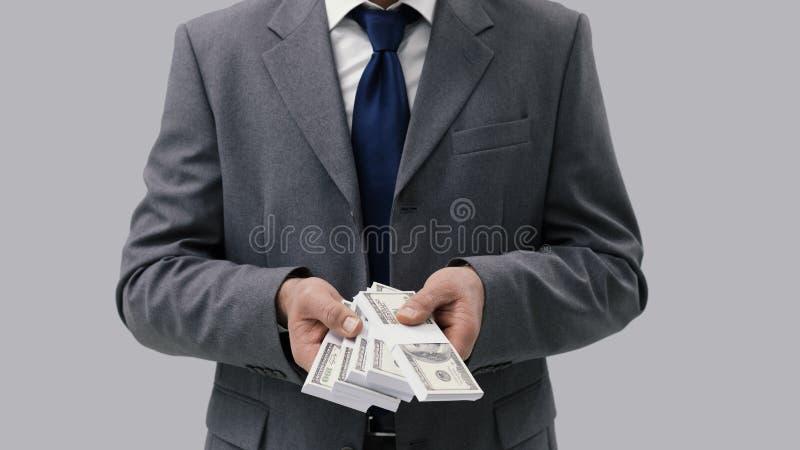 Homem de negócios que guarda o dinheiro do dinheiro imagens de stock