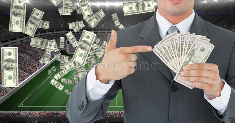 Homem de negócios que guarda o dinheiro no estádio de futebol que representa a corrupção imagem de stock