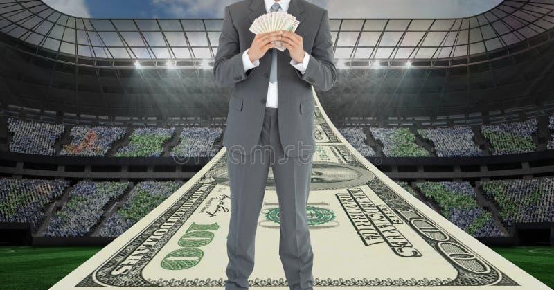 Homem de negócios que guarda o dinheiro no estádio de futebol que representa a corrupção imagens de stock royalty free
