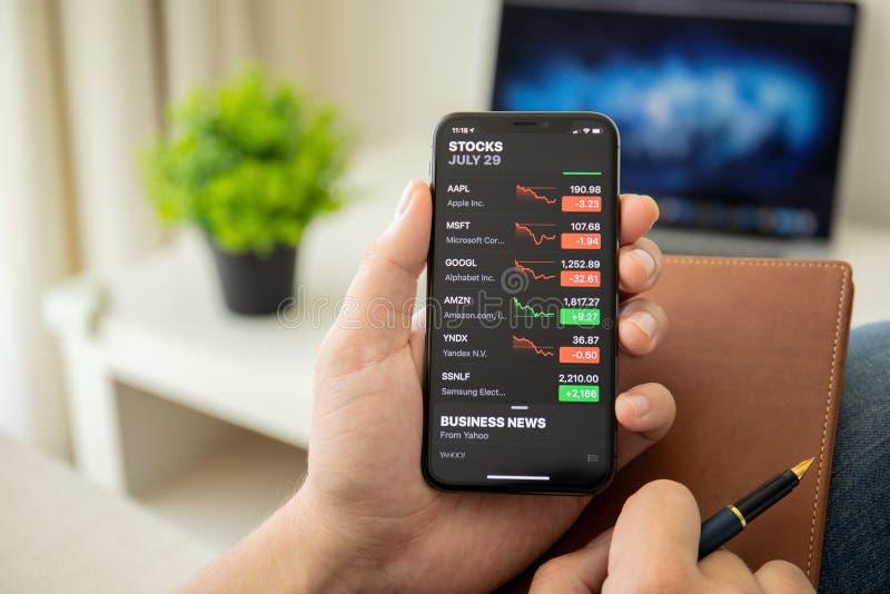 Homem de negócios que guarda o iPhone X com os estoques da aplicação de Apple fotografia de stock royalty free