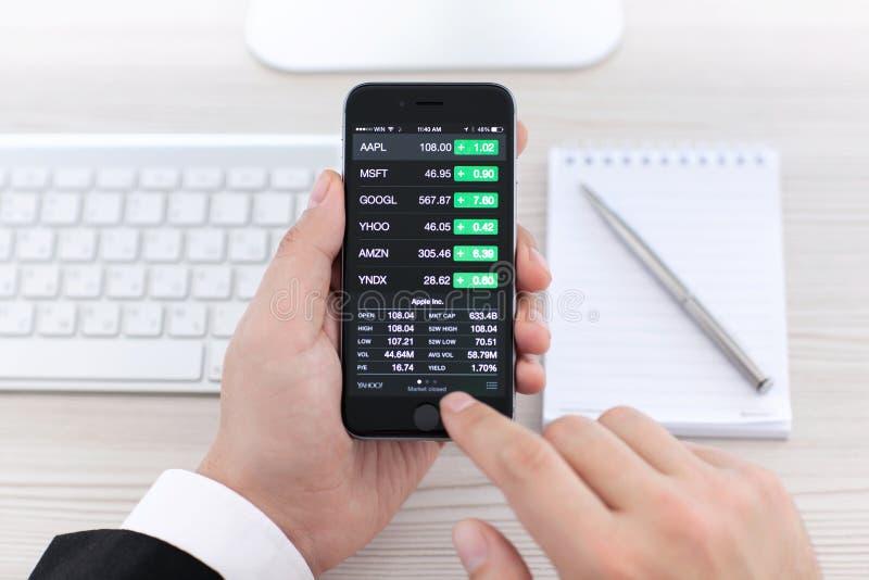 Homem de negócios que guarda o iPhone 6 com os estoques da aplicação de Apple imagens de stock royalty free
