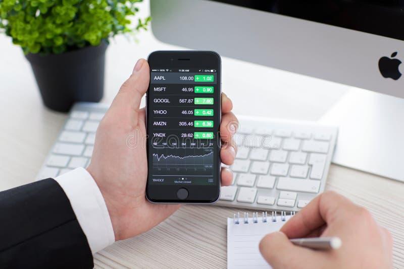 Homem de negócios que guarda o iPhone 6 com os estoques da aplicação de Apple fotos de stock royalty free