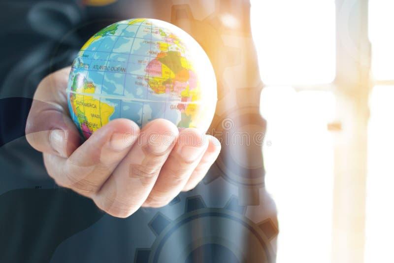 Homem de negócios que guarda o mapa da bola do modelo do globo da terra nas mãos Conceito imagem de stock royalty free
