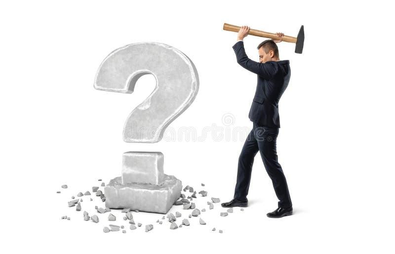 Homem de negócios que guarda o martelo grande para deixar de funcionar o ponto de interrogação feito da pedra fotografia de stock