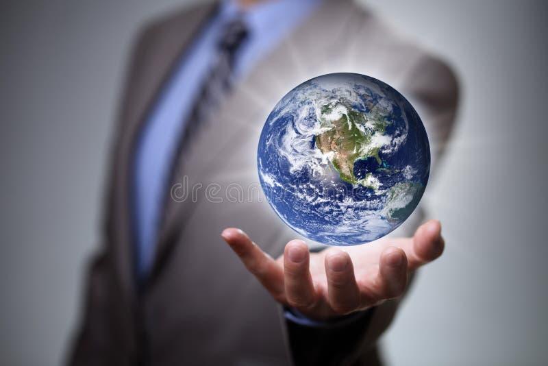 Homem de negócios que guarda o mundo em suas mãos imagens de stock royalty free
