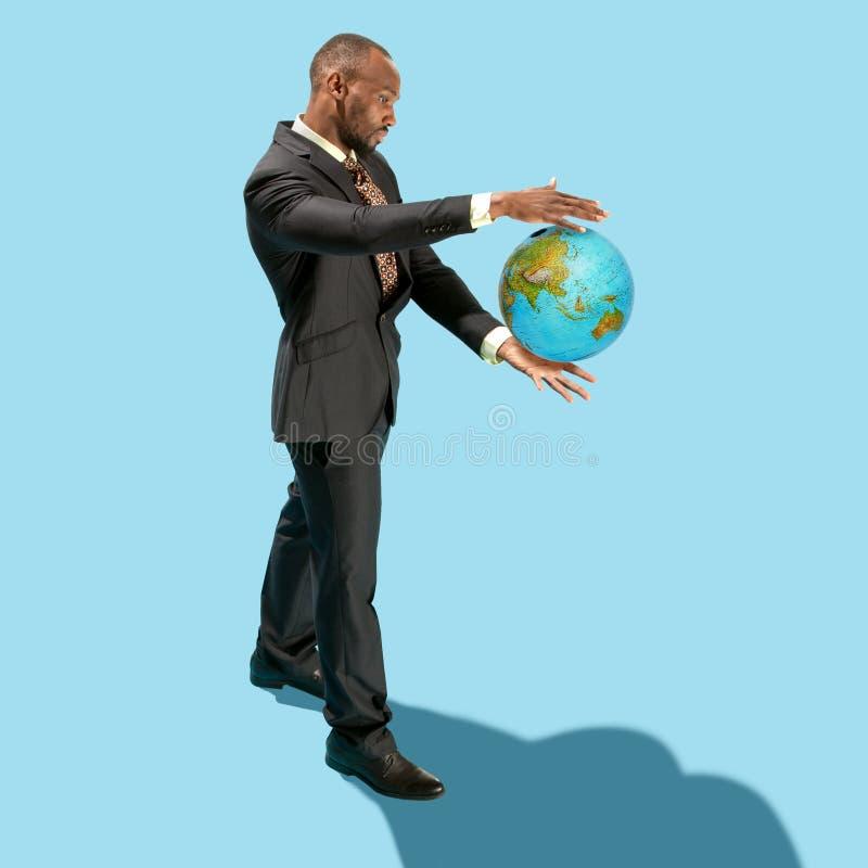 Homem de negócios que guarda o mundo na palma da mão o conceito para o negócio global, comunicações, política foto de stock