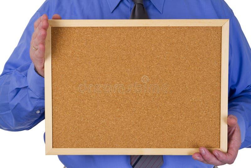 Homem de negócios que guarda o quadro de anúncios vazio fotos de stock