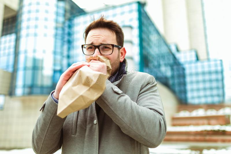 Homem de negócios que guarda o saco de papel sobre a boca como se tendo um ataque de pânico fotografia de stock