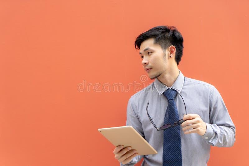 Homem de negócios que guarda o tablet pc digital no fundo com c imagens de stock royalty free