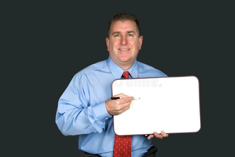 Homem de negócios que guarda o whiteboard vazio fotos de stock