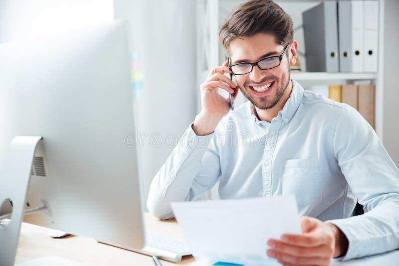 Homem de negócios que guarda originais e que fala no telefone celular no escritório fotografia de stock