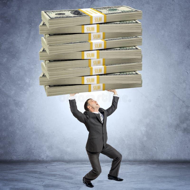 Homem de negócios que guarda a pilha grande pesada de dinheiro fotografia de stock royalty free