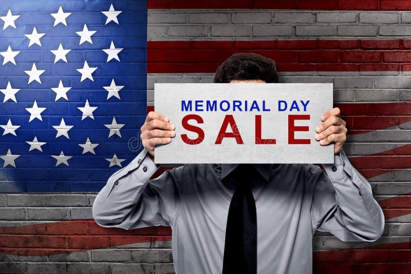 Homem de negócios que guarda a placa com sinal da venda do Memorial Day imagens de stock royalty free