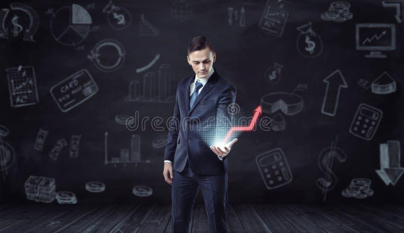 Homem de negócios que guarda a projeção do computador da seta vermelha de aumentação no fundo com esboços econômicos imagem de stock
