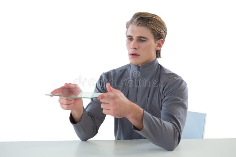 Homem de negócios que guarda a relação de vidro ao sentar-se na tabela imagem de stock royalty free