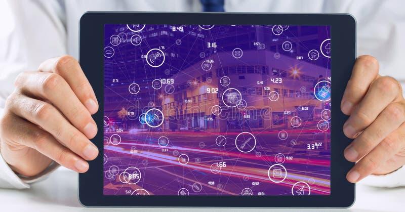 Homem de negócios que guarda a tabuleta com a tela da cidade da noite com conectores imagem de stock