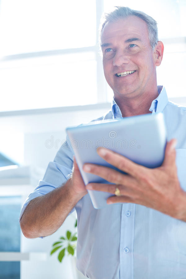 Homem de negócios que guarda a tabuleta digital no escritório imagens de stock royalty free