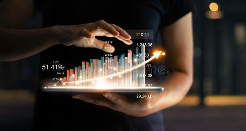 Homem de negócios que guarda a tabuleta que mostra a estatística virtual do holograma fotografia de stock royalty free