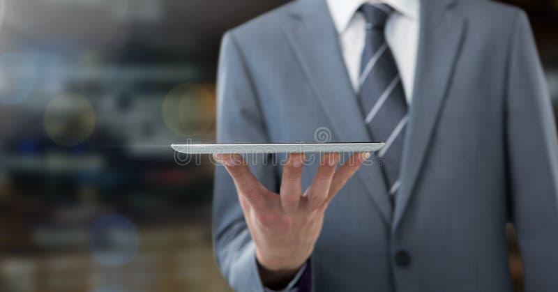 Homem de negócios que guarda a tabuleta na cidade da noite fotografia de stock