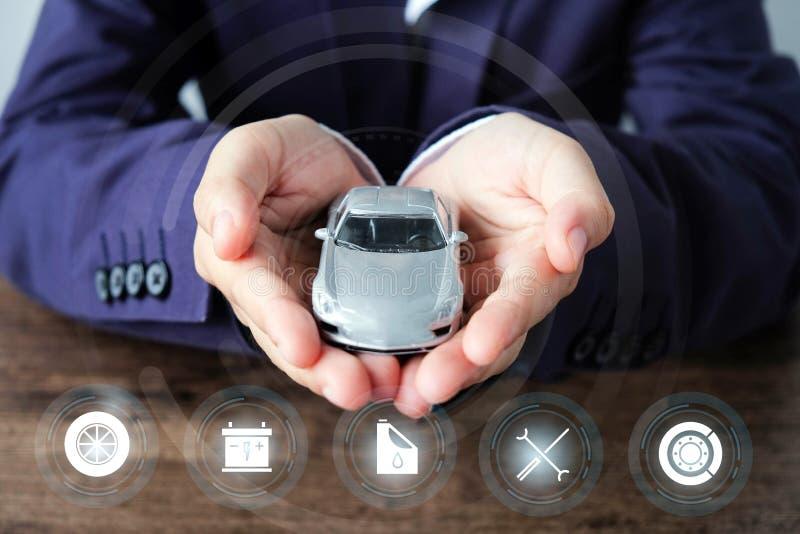 Homem de negócios que guarda um carro com ícones do serviço no fundo de madeira, no conceito do carro que verificam, no reparo e  fotos de stock