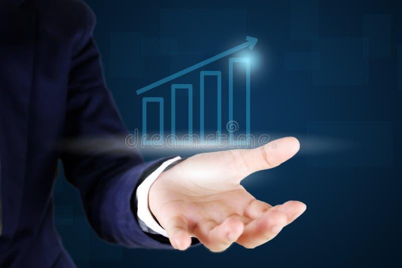 Homem de negócios que guarda um gráfico do crescimento imagem de stock