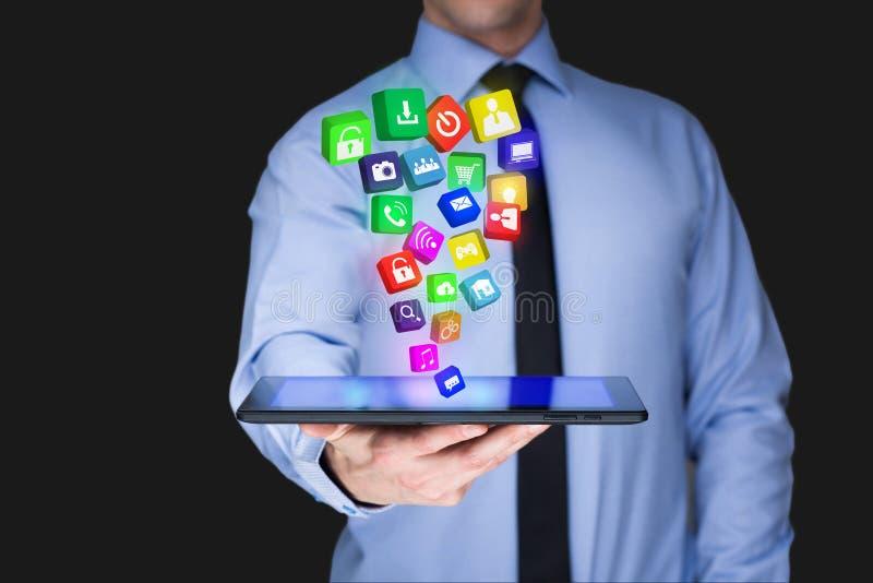 Homem de negócios que guarda um PC da tabuleta com ícones móveis das aplicações na tela virtual Internet e conceito do negócio foto de stock royalty free