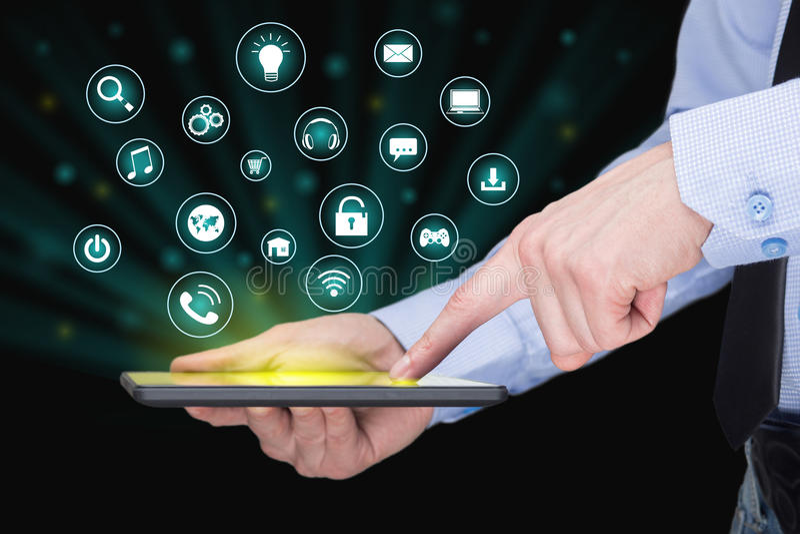 Homem de negócios que guarda um PC da tabuleta com ícones móveis das aplicações na tela virtual Internet e conceito do negócio imagens de stock