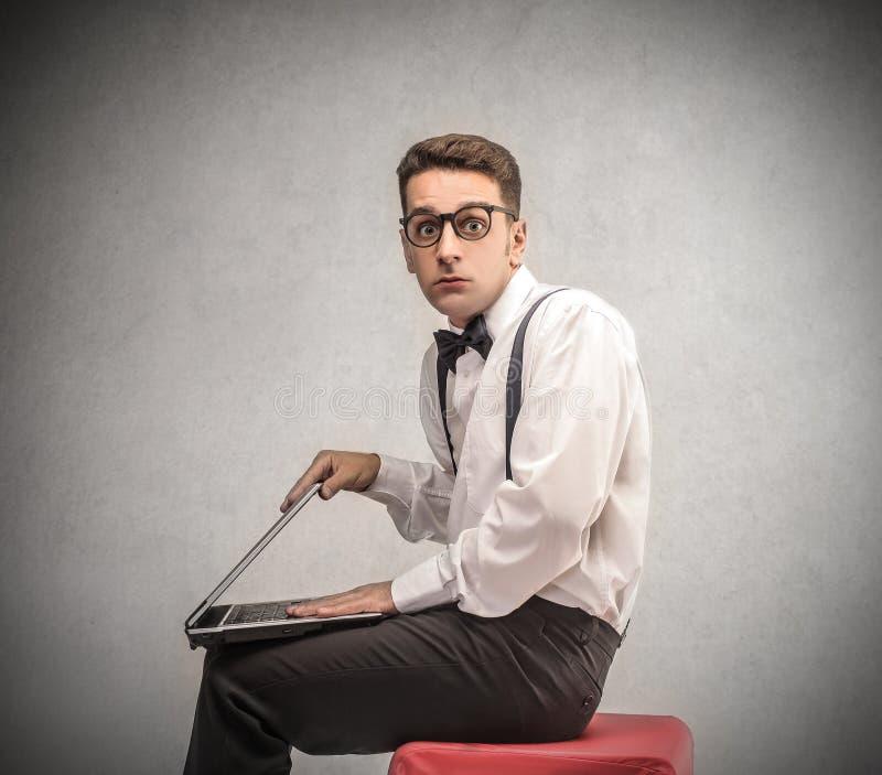Homem de negócios que guarda um portátil fotografia de stock