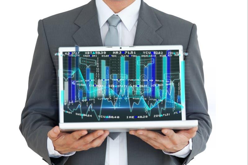 Homem de negócios que guarda um portátil com gráficos fotos de stock royalty free