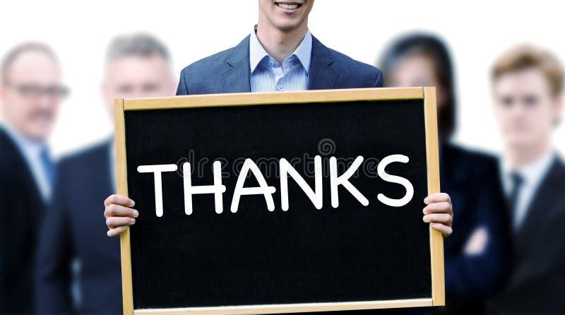 Homem de negócios que guarda um sinal com os agradecimentos da palavra imagem de stock