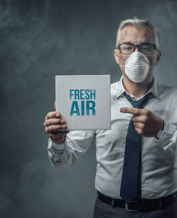Homem de negócios que guarda um sinal e uma poluição do ar foto de stock royalty free