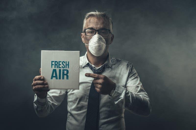 Homem de negócios que guarda um sinal e uma poluição do ar imagens de stock