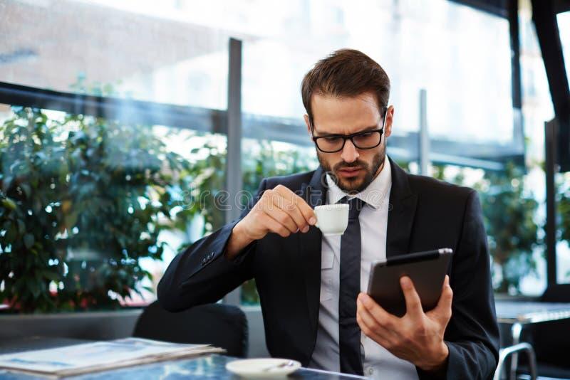 Homem de negócios que guarda a xícara de café quando notícia lida na tabuleta imagem de stock royalty free