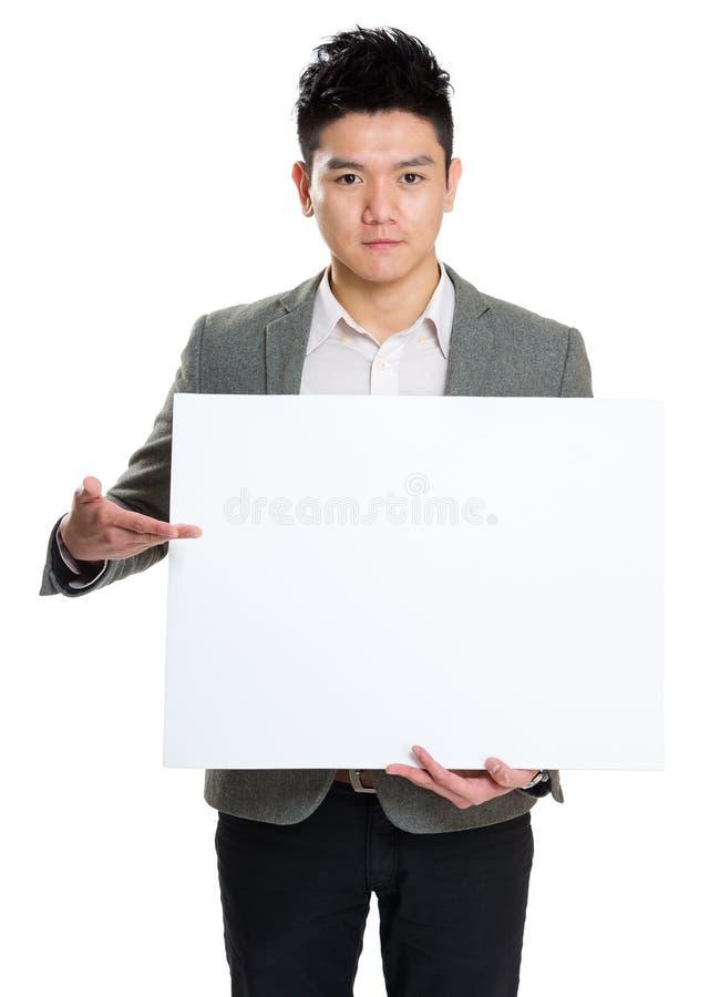 Homem de negócios que guardara o quadro de avisos vazio fotografia de stock royalty free