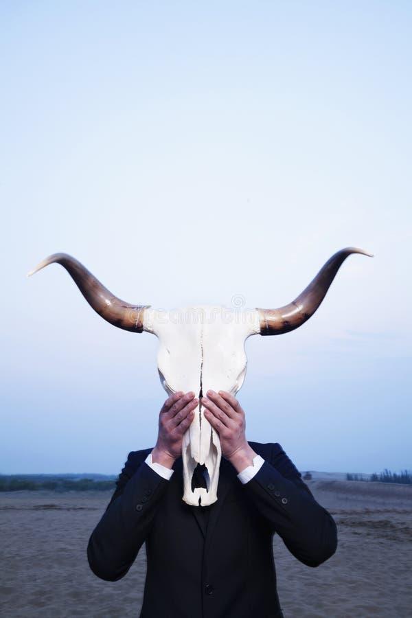 Homem de negócios que guardara um crânio animal na frente de sua cara no deserto imagens de stock