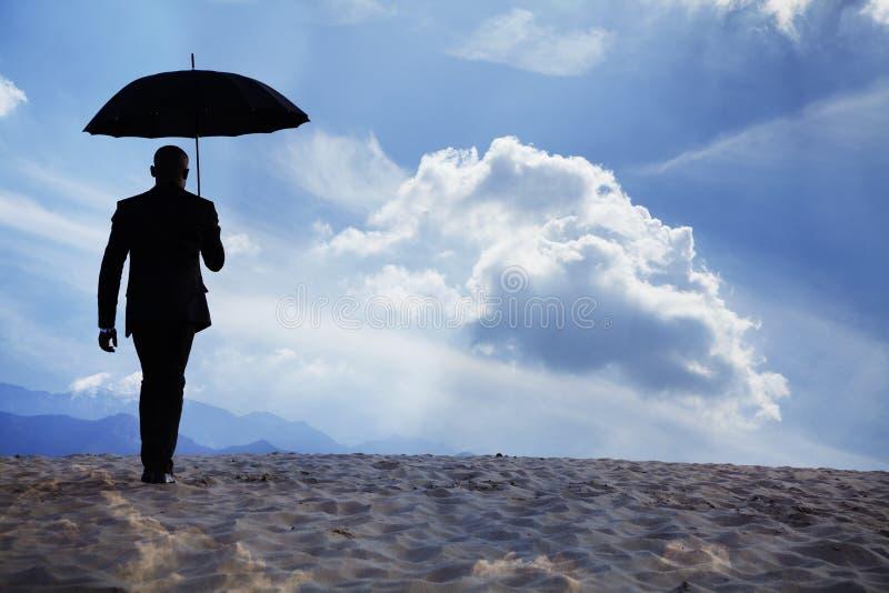 Homem de negócios que guardara um guarda-chuva e que anda afastado no meio do deserto com nuvens dreamlike imagens de stock royalty free